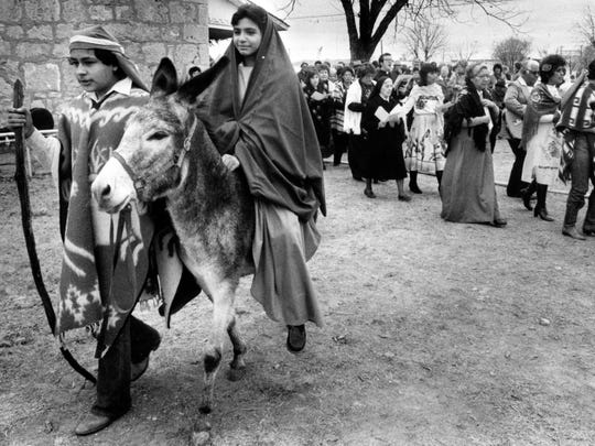 Actors playing the part of Joseph and Mary lead a parade of singers during Los Posadas during the Christmas at Old Fort Concho celebrations in 1982.