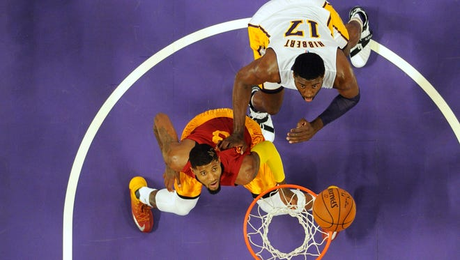 Los Angeles Lakers center Roy Hibbert (17) and Indiana Pacers forward Paul George (13) look up for the ball in the first half at Staples Center.