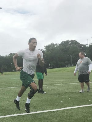 Former Rickards High School quarterback D.J. Phillips races to the sideline during conditioning drills.