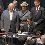 Gov. Andrew Cuomo signs the SAFE Act in a ceremony in Rochester in January 2013.