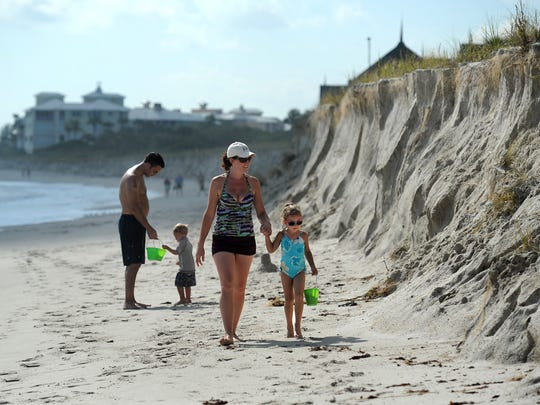 The warm holiday weather allows families to take leisurely walks along Treasure Coast beaches like this family combing the shoreline looking for shells at the Disney Vero Beach Resort (background) off Wabasso Beach.