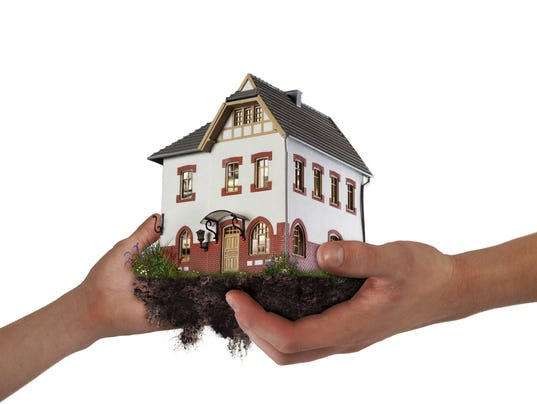 Hands holding a house. The concept of relocation, mortgage, inheritance,