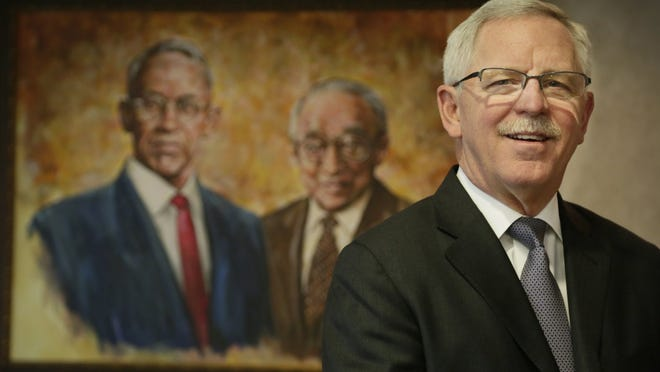 David Provost, chairman and CEO of Talmer Bank in Troy, poses for a portrait with a painting of his grandfather John Van Neste Talmage, left, and M. Manuel Merzon.