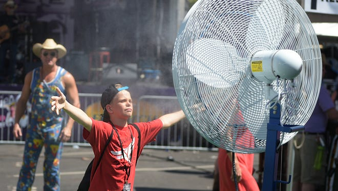 Ryder Powell, 10, uses a misting fan to cool down during the CMA Music Festival on Friday, June 10, 2016.