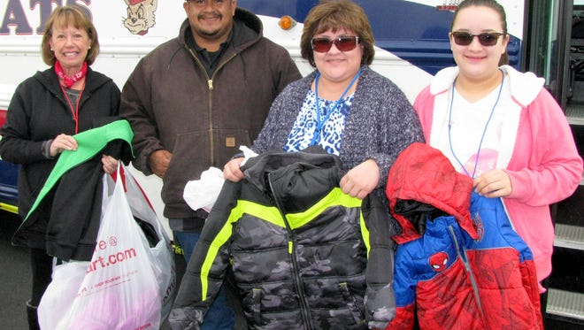 """Victor Pena donated several winter jackets on behalf of The Rockin' the Streets Bike Run in Memory of Ramon """"Momo"""" Pena III. Accepting the jackets are Luna County Coats for Kids volunteers, from left, Ally Read, Niki and Celeste Casillas."""