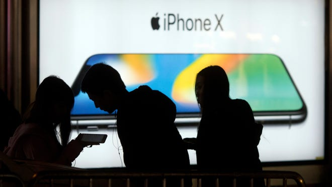 Youths use their mobile phones near an advertisement for iPhone X in Beijing, China, on Nov. 6, 2017.