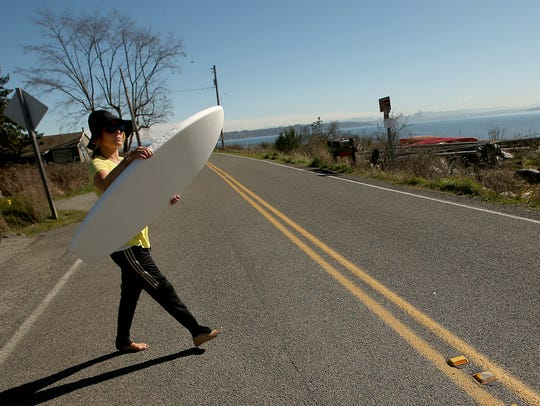 Sarah Dean carries her training surf board across the
