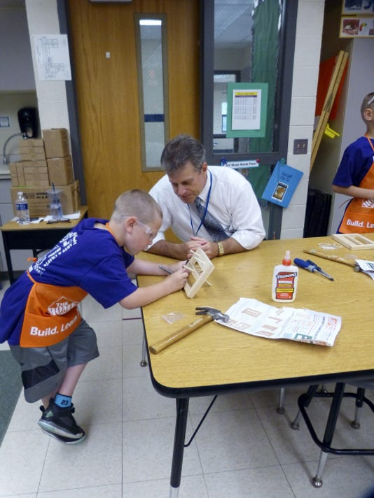 Northern Lebanon School District Superintendent Don Bell watches Lickdale Elementary School Sage Wanamaker work on a project at the school's recent reading carnival.