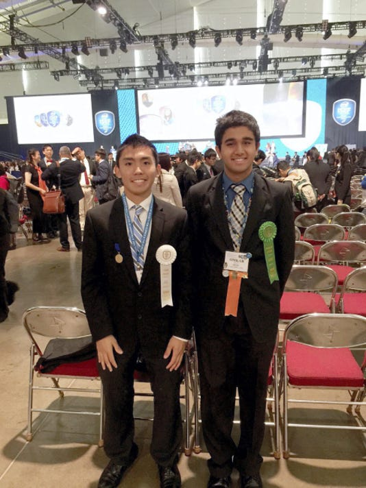 Alec Jason Gayrama, left and Omkar Kane, right, stand with their ribbons as winners at the Intel International Science Fair in Pittsburgh.
