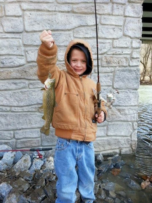Eight-year-old Connor Hooper is all smiles as he holds up a nice brown trout he caught during last week's chilly Regional Mentored Youth Trout Day.