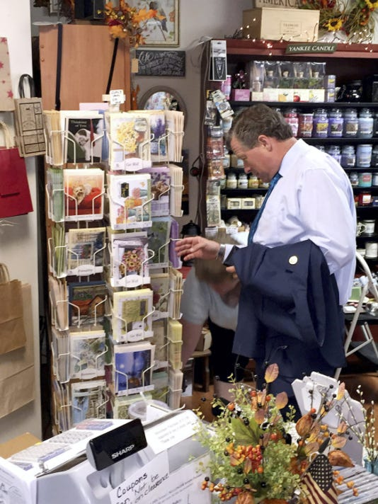 Rep. Charlie Dent (R-15) looks at anniversary cards with Lauri Stewart (partially obscured) when he visited her shop, Stewart's Gift Peddler, during his walking tour of Annville on Wednesday.