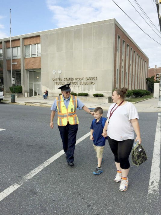 Lebanon crossing guard Raymond Kohr escorts Jeanne Lentini and her 6-year-old son, Luciano, across Eighth Street at Chestnut Street in Lebanon on their way to Harding Elementary School on the first day of classes last Wednesday. Kohr, of Lebanon, has been a crossing guard for two decades.