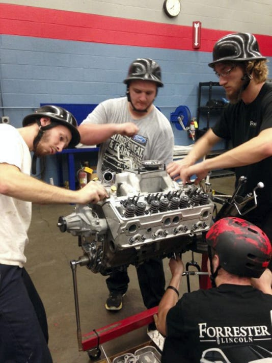 Franklin County Career and Technology Center students Devin Flasher, left, Shawn Robinson and Brandon Kennedy on Tuesday evening practice taking apart an engine and putting back together.