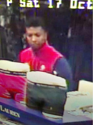 Police are searching for this man who they say punched an employee who tried to stop them from making off with stolen merchandise.
