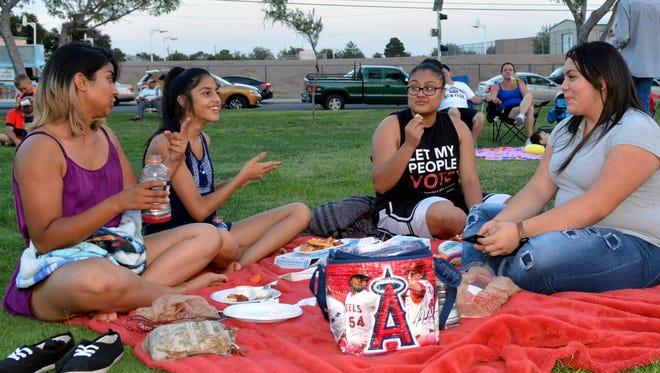 Aracelia Delgado, left, Lizbeth Delgado, Liliana Ortega and Yadira Flores enjoy a few laughs and snacks before the start of the Movie in the Park on Saturday, July 16, 2016.