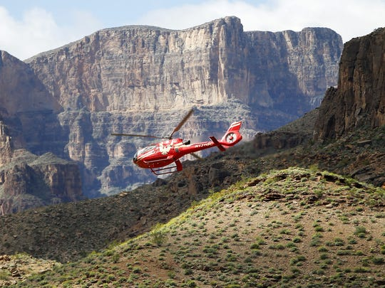 A tour helicopter flies over the Colorado River on