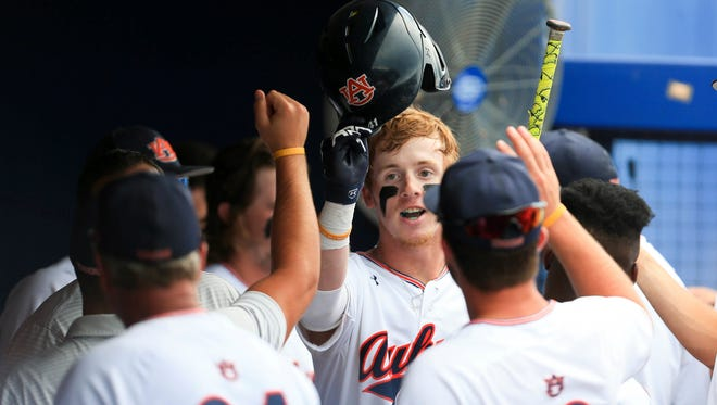 Auburn outfielder Steven Williams celebrates in the dugout after hitting a home run against Florida during an NCAA Super Regional college baseball game Sunday, June 10, 2018, in Gainesville, Fla.