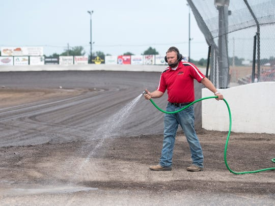 Speedway employee Lance Allen sprays down the entry to the track to help settle the dust before the 2018 Summer National late model races at Tri-State Speedway on Sunday, June 24, 2018.