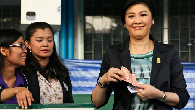 In this Feb. 2, file photo Thai Prime Minister and Pheu Thai party leader Yingluck Shinawatra, right, smiles as she poses before casting her ballot for the general election at a polling station in Bangkok.