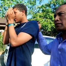 An Indonesian police officer escorts Tommy Schaefer, left, as he is brought to the police station for questioning on Aug. 13, 2014.