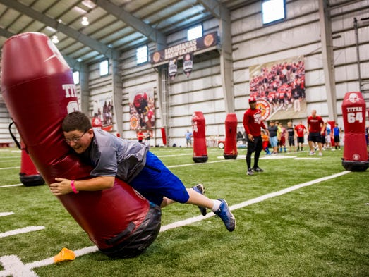 Connor Diaz, 11, tackles a dummy while running drills