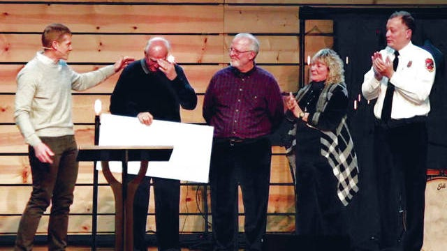 Crossroads to Home Cafe founder Con Vrails reacts to receiving a $65,500 check for the nonprofit from Maury Hills Church lead pastor Russ Adcox, left. Board members Mark Kirschbaum, Lori Bergland and Ty Cobb also were present for the surprise presentation.