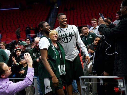 Spartans fan Jodi Stevens, center, poses for a photo