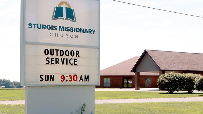 Sturgis Missionary Church advertises its outdoor services. A large, open-sided tent has been placed behind the church building.