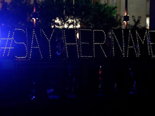 """Protestors hold up a lighted sign reading """"#say her name"""" during a vigil for Sandra Bland, Tuesday evening, July 28, 2015, in Chicago. Bland died in a Texas county jail after the traffic stop for failing to use a turn signal escalated into a physical confrontation. Authorities have said Bland hanged herself, a finding her family disputes. The death has garnered national attention amid increased scrutiny of police treatment of blacks in the wake of several high-profile police-involved deaths."""