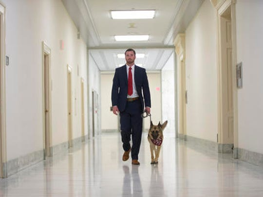 """Military veteran Cole Lyle, who suffers with PTSD, walks with his dog Kaya in the hallways of Rayburn House Office building on Capitol Hill in Washington, prior to testifying before the House National Security subcommittee hearing on """"Connecting Veterans with PTSD with Service Dogs."""""""