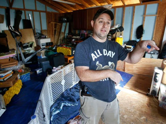 In this Thursday, Nov. 3, 2016 photo, Jason Meier gestures as he talks about the storage shed he plans to move his family into while they repair his flood damaged home in Virginia Beach, Va.. Hundreds of homes in the area were damaged from floodwaters from the remnants of Hurricane Matthew.