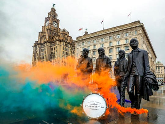 "Smoke flares are set off during a photo call by the Beatles' statue on Liverpool's waterfront, in Liverpool, England, Wednesday, March 22, 2017. The city of Liverpool is getting set to celebrate the half-centenary of ""Sgt. Pepper's Lonely Hearts Club Band,"" one of the most influential albums by local heroes The Beatles."