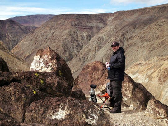 In this photo taken Feb. 28, 2017, photographer Jason O. Watson waits on a cliff overlooking the nicknamed Star Wars Canyon in Death Valley National Park, Calif. Military jets roaring over national parks have long drawn complaints from hikers and campers. But in California's Death Valley, the low-flying combat aircraft skillfully zipping between the craggy landscape has become a popular attraction in the 3.3 million acre park in the Mojave Desert, 260 miles east of Los Angeles.