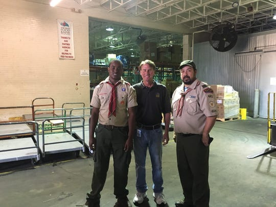 Steven Prescott, left, stands with David Stephens, community relations manager at the Mid-South Food Bank, and his scoutmaster from Troop 441 in Memphis, Carlos Tellez.