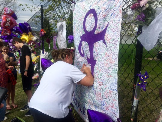 A woman writes on memorial sheet adorned with the symbol Prince once used to identify himself outside Paisley Park in Chanhassen, Minn., Saturday, April 23, 2016. The music superstar was pronounced dead at his Paisley Park estate near Minneapolis on Thursday. He was 57.