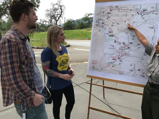 Tourists look over a map of the Giant Sequoia National Monument while visiting Sequoia National Park.