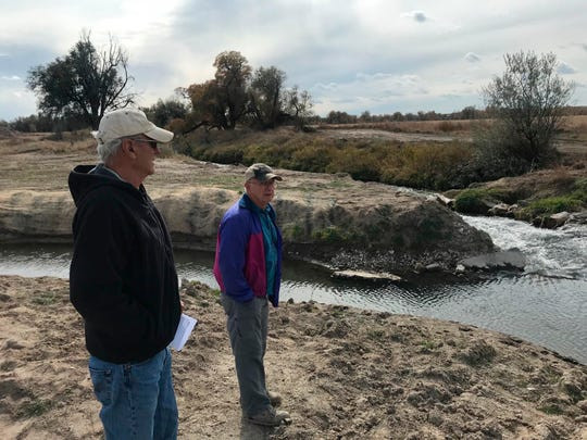 Bob Smith, left, and Bruce Rolls look over an irrigation drainage ditch being diverted near Mitchell, Neb. The first-of-its kind project could revive trout fishing in the Panhandle area after it disappeared decades ago.