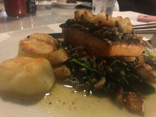 The salmon Grenoblaise is topped with brown butter, capers, and garlic croutons.
