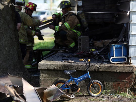 Muncie firefighters at the scene of a May 8 house fire that killed 3-year-old Clayton Carnes.