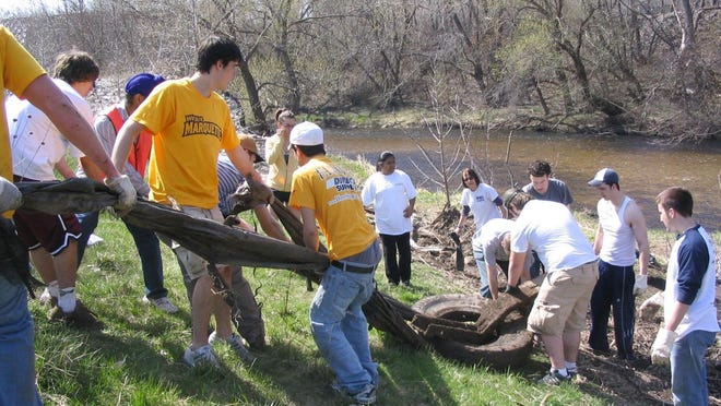 Marquette University students clean up trash along the Menomonee River near the Hank Aaron trail as part of an Earth Day cleanup event.