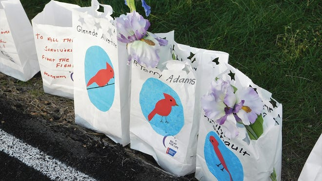 Luminaria bags with the names of loved ones written on them line a portion of the track at Mount Wachusett Community College during the 2019 Relay for Life in Gardner.