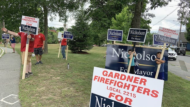 Michael Nicholson's supporters hold signs at Monument Park during Gardner's special mayoral election on Tuesday, June 30.