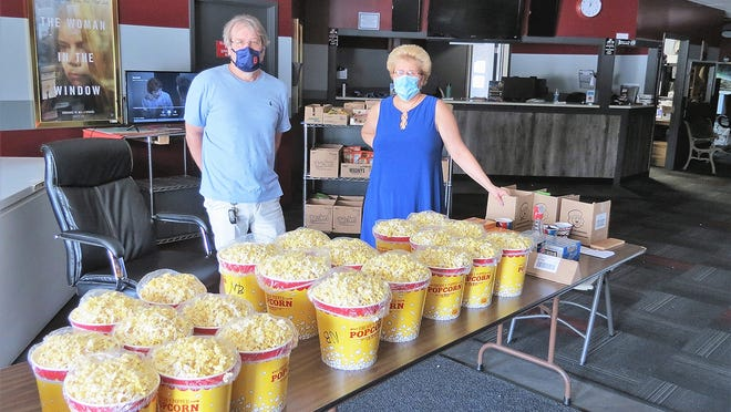 Though Gardner Cinemas has not reopened for moviegoers, popcorn, candy and ice cream are available during the weekend at the drive-up in front of the business. Shown in the photo are owners Chris Daigle and Sandy Worthley.