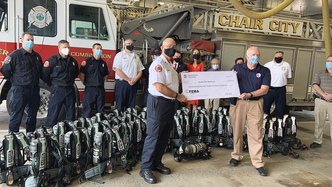 Gardner Fire Chief Richard Ares receives a ceremonial check from FEMA representative David Parr for the purchase of new breathing equipment for each member of the department. Looking on are fire department staff and elected city officials during a recent gathering at the fire station. Ares retired on Sept. 30.