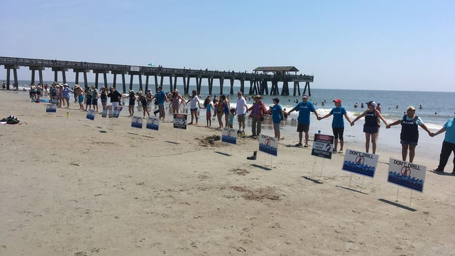 """Participants in """"Hands Across the Sand"""" join hands on Tybee in May 2019 in a show of solidarity against offshore drilling and seismic testing."""