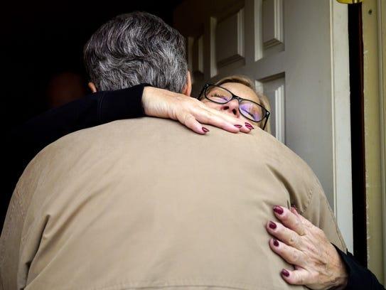 Shirley Evans hugs Rick Fredericksen as he arrives