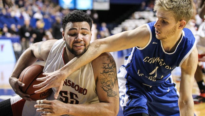 Bo Schuh tries to reach around and tie up Owensboro's Justin Miller, but Owensboro got a time out first during their semifinal game in the Boys Sweet Sixteen at Rupp Arena in Lexington, Saturday, March 21, 2015.