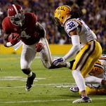 BATON ROUGE, LA - NOVEMBER 08:  T.J. Yeldon #4 of the Alabama Crimson Tide tries to avoid a tackle by Kwon Alexander #4 and Jalen Collins #32 of the LSU Tigers  during a game at Tiger Stadium on November 8, 2014 in Baton Rouge, Louisiana.  (Photo by Chris Graythen/Getty Images)