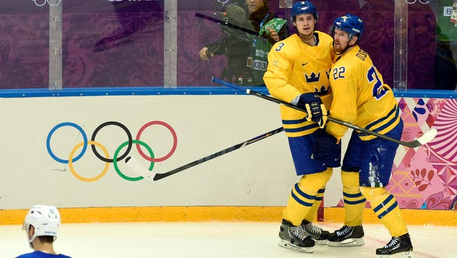 Sweden forward Daniel Sedin (22) celebrates with defenseman Oliver Ekman-Larsson (3) after scoring a goal against Slovenia.