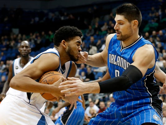 Minnesota Timberwolves' Karl-Anthony Towns, left, encounters Orlando Magic' Nikola Vucevic of Montenegro as he drives in the first quarter of an NBA basketball game, Tuesday, Dec. 1, 2015, in Minneapolis. (AP Photo/Jim Mone)